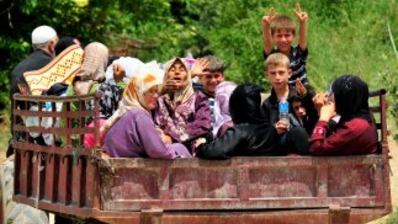 Centenares de sirios cruzaron la frontera el lunes hacia campamentos de...