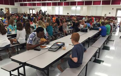 El jugador Travis Rudolph y el niño Bo Paske almuerzan en una caf...