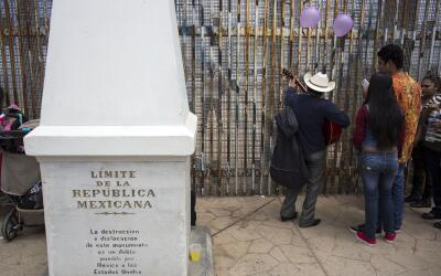 Un grupo de personas reunidas en el lado mexicano de la frontera con Est...