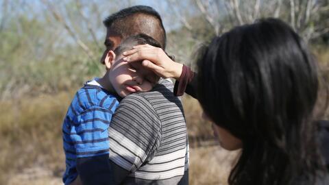 Una pareja de migrantes centroamericanos con un niño en brazos trata de...