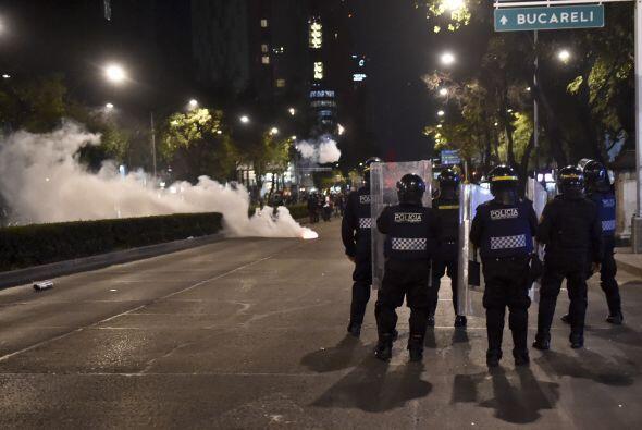 Elementos de la policía antidisturbios se resguardan de los petardos arr...