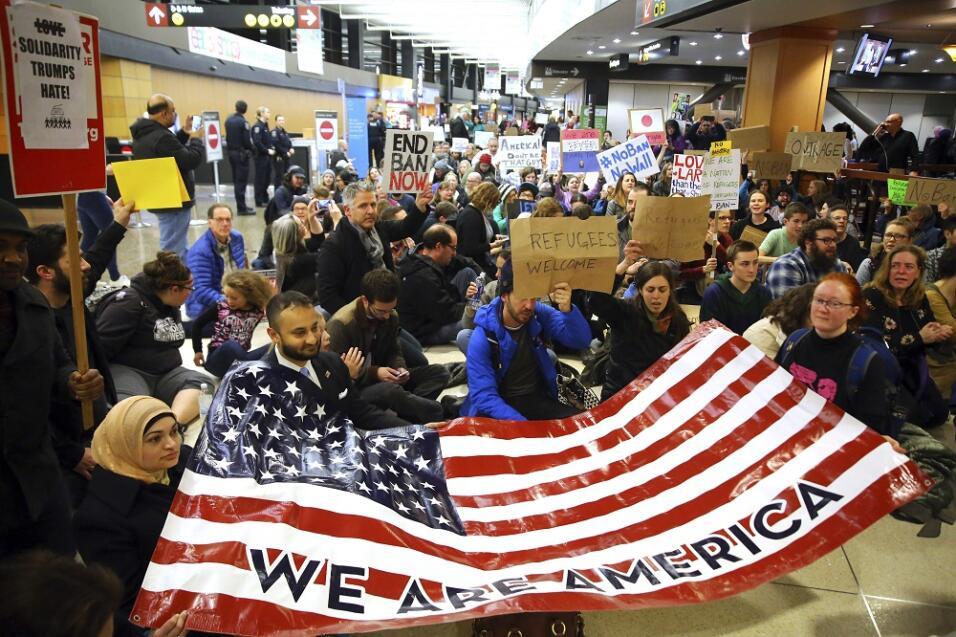 Manifestantes en el Seattle-Tacoma International Airport con una bandera...
