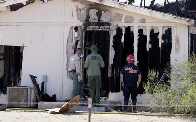 Investigadores de incendios y detectives de homicidios en el lugar quemado.