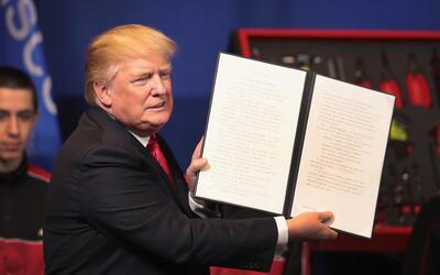 El presidente Donald Trump muestra el decreto donde ordena revisar el pr...