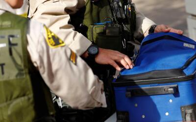 Un agente del Sheriff de Los Ángeles revisa una maleta a la entra...