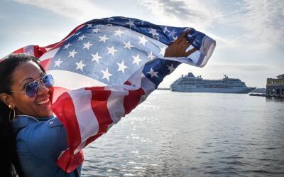 Una mujer con una bandera de EEUU en el Malecón de La Habana durante la...