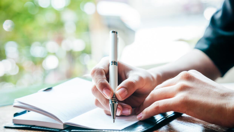 Persona escribiendo en su diario