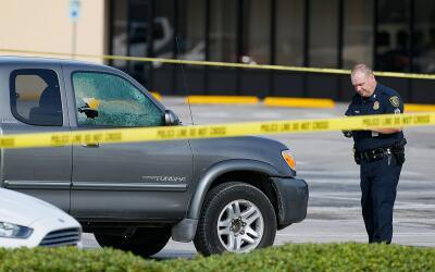 Un policía revisa un auto que recibió disparos en el tiroteo.
