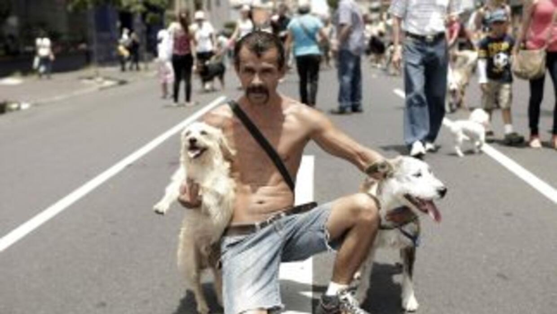 Un hombre posa con sus perros durante una marcha en la que participaron...