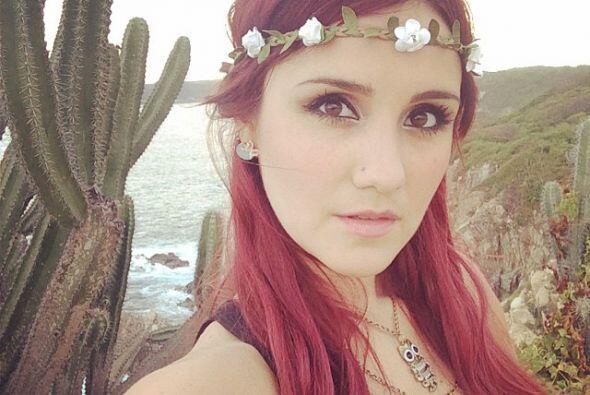Dulce María con un hermoso paisaje y una corona de flores.
