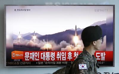 Un soldado surcoreano pasa junto a un programa noticioso televisivo que...