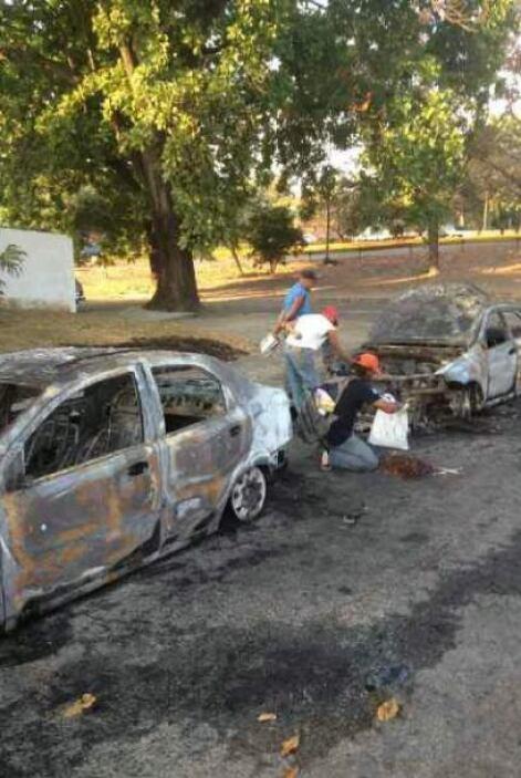 Carros destruidos durante una protesta contra el gobierno en El Trigal,...