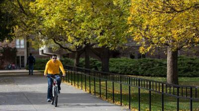 Un joven en bicicleta por la Universidad de Colorado, en boulder.