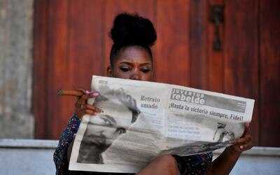 Una mujer se fuma un puro en las calles de La Habana mientras lee el per...