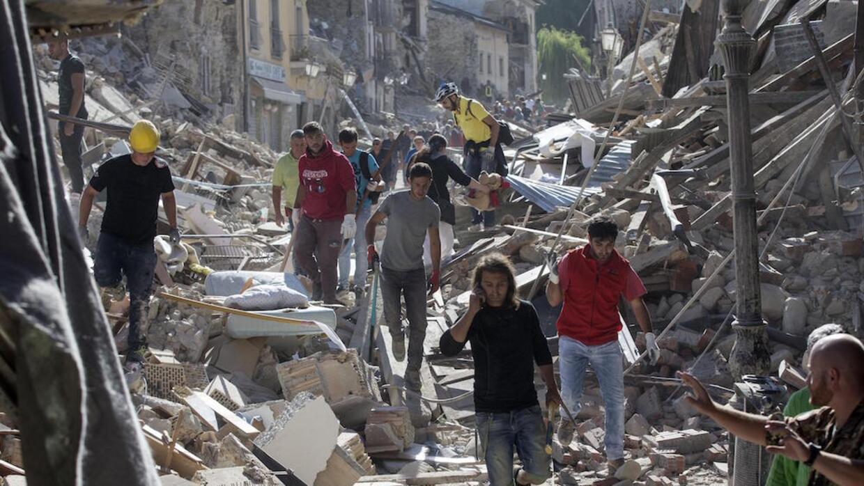 Sobrevivientes y rescatistas caminando sobre los escombros en Amatrice