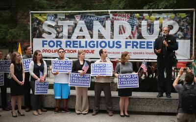Fr. Thomas Loya (R) speaks at a rally in support of religious freedom af...