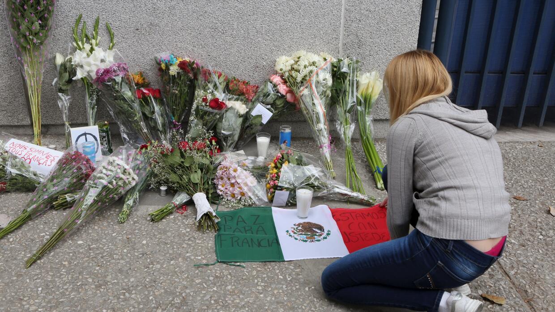 Una mujer rinde homenaje a las víctimas en la embajada francesa en Méxic...