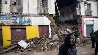 Un hombre pasa frente a una casa completamente destruída por el terremot...