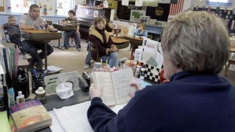Maestra le lee a estudiantes dentro del salón de clases.