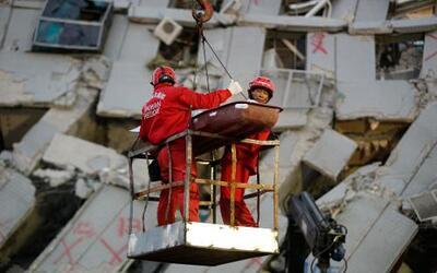 Dos socorristas transportan a una víctima retirada de entre los restos d...