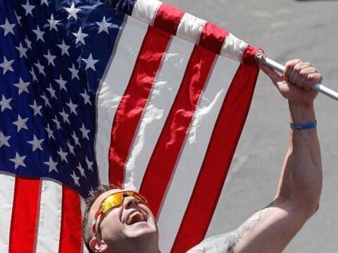 Un corredor sostiene una bandera estadounidense durante el Marató...