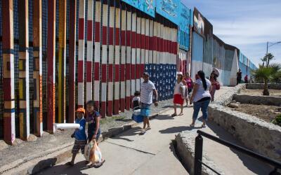 Una familia camina cerca de la valla metálica que divide a Playas...