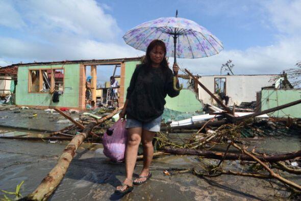 Habitantes de la ciudad de Tacloban cargan un ataúd que fabricaron ellos...