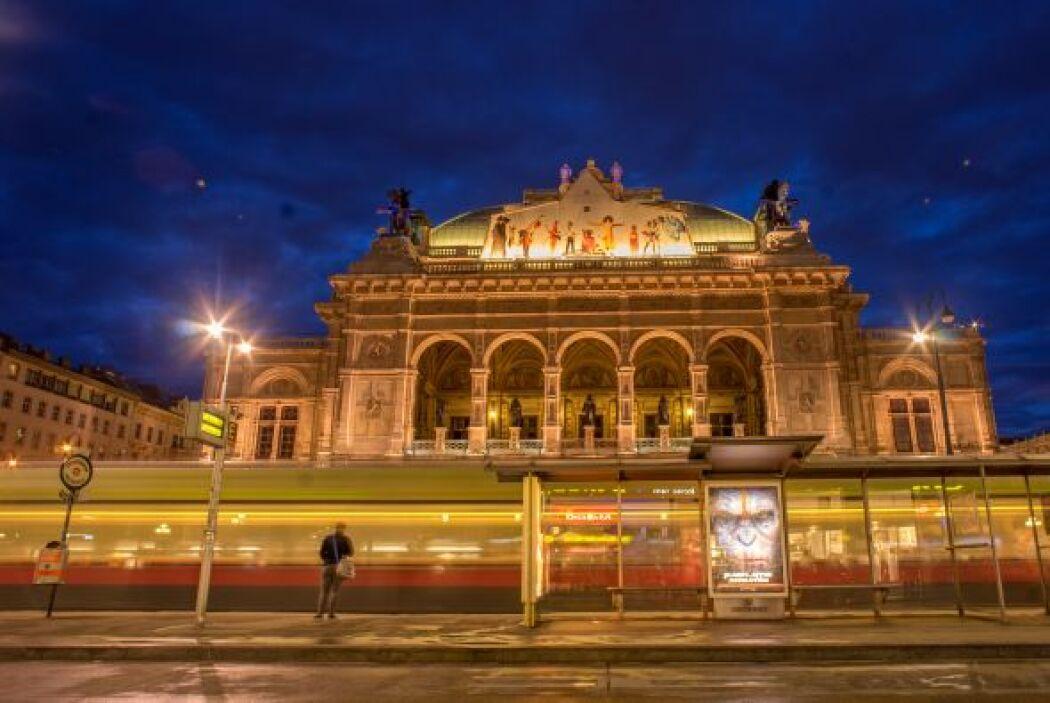Una mujer espera a un tranvía de la ciudad frente al teatro de Opera Wie...