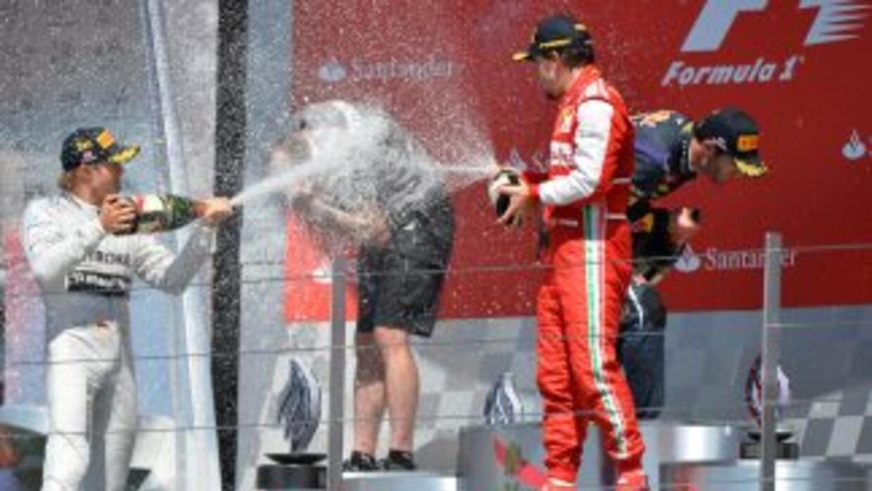 Rosberg es bañado en champange por sus escoltas.
