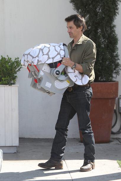 Aquí vemos al feliz papá llevando a su retoño en br...