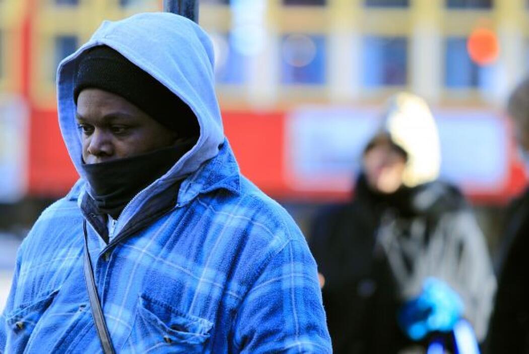 Enfundados en sus abrigos, la gente espera el autobús de la calle de Can...