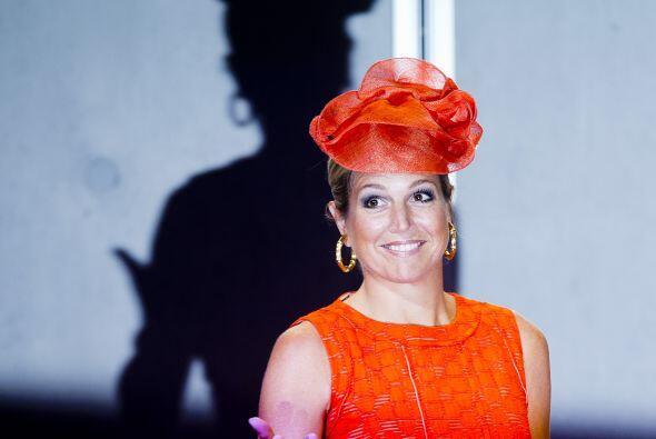 De naranja, con un vestido con un corte 'lady' y con un llamativo tocado...