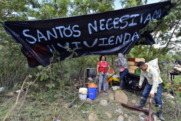 Una familia colombiana se mantiene junto a una pancarta que dice 'Santos...