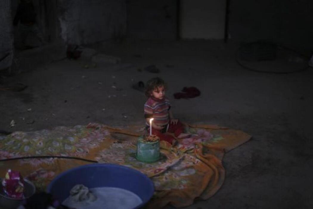 Un niño junto a una vela en el campo de refugiados de Jabaliya durante u...