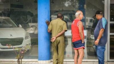 Cubanos miran los coches a la venta en una concesionaria de autos en La...