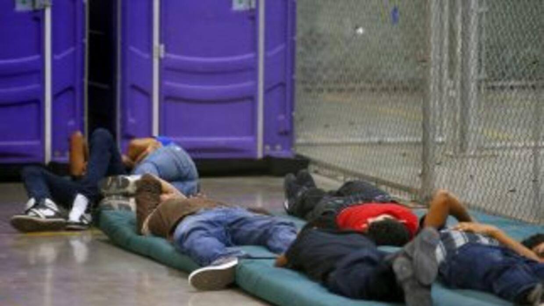 Niños indocumentados duernes en un centro improvisado de la Patrulla Fro...