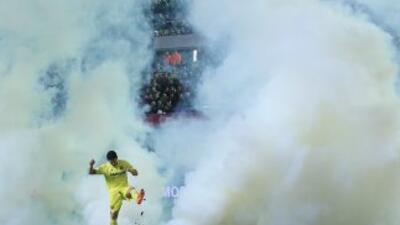 Jonathan Pereira trata de apagar la bomba de humo lanzada al campo.