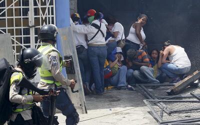 Un grupo de manifestantes de la oposición se resguarda del ataque...