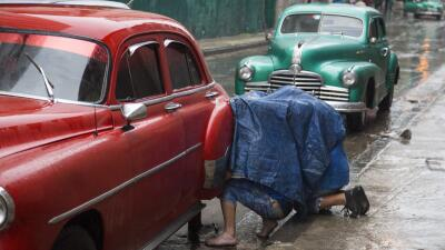 Mecánicos reparan el eje de un taxi colectivo en La Habana, Cuba.
