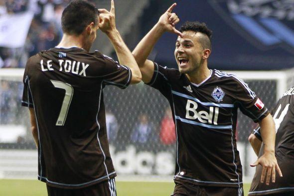 Sebastien Le Toux y Davide Chiumiento del Vancouver Whitecaps al anotar...