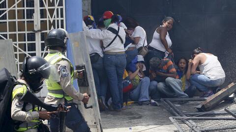 Un grupo de manifestantes de la oposición se resguarda del ataque con bo...