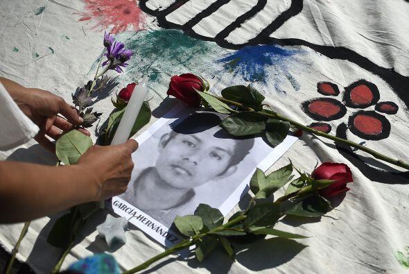 Un grupo de estudiantes colocó veladoras y flores  sobre los retratos de...