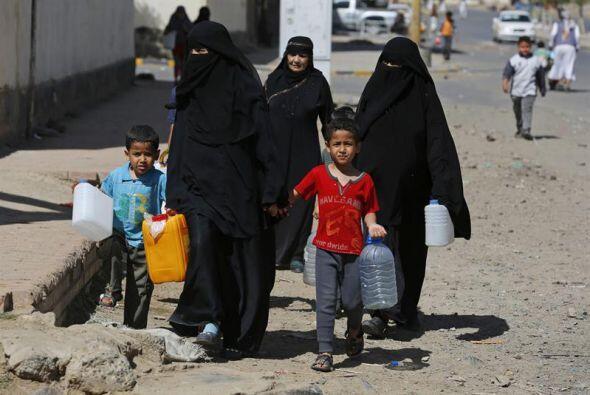 Mujeres yemeníes ataviadas con el burka se dirigen junto a sus hijos a u...