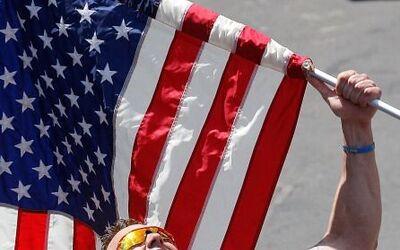 Un corredor sostiene una bandera estadounidense durante el Maratón de Bo...