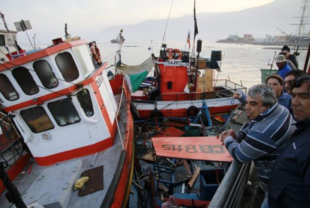 Varias personas observan embarcaciones tras el terremoto. Algunas tienen...
