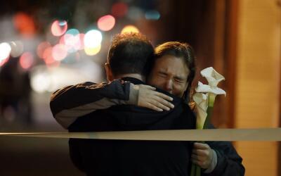 Dos personas se abrazan este domingo en los alrededores del lugar donde...