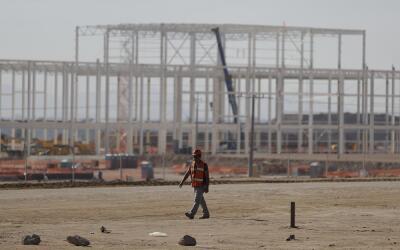 Un hombre camina frente a una fábrica en construcción virt...