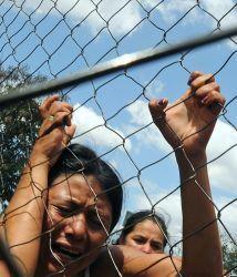 Una mujer llora junto a la cerca que delimita los terrenos de la prisión...