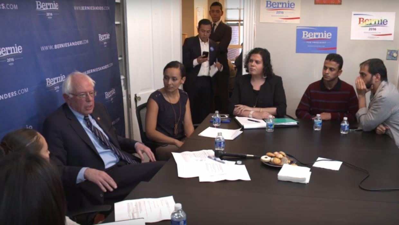 Bernie Sanders junto a varios inmigrantes.