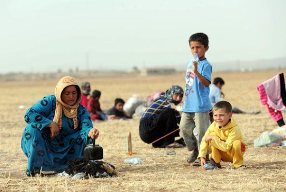 Niños refugiados kurdos sirios rodean a su madre mientras ella hace té....